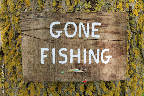 Valokuva  gone fishing sign written a wooden plaque hanging on a tree