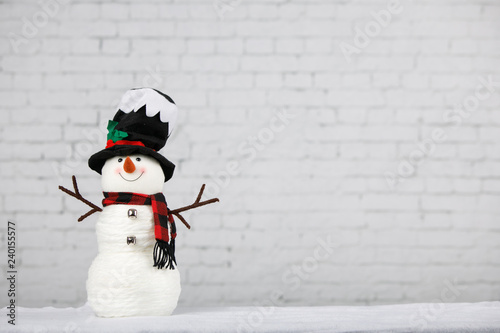 Fotografia, Obraz  Snowman against winter white brick wall background