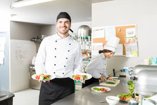 Young Cook Smiling While Presenting Dish In Kitchen