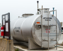 A Storage Tank For Jet Fuel. The Fuel Is JET A1. Fire Extinguisher On A Sign On The Left. Overcast Sky.