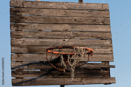 Old and rusty basketball hoop with tangled net, on an old wooden backboard Tapéta, Fotótapéta