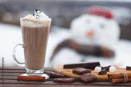 Fotografie, Obraz  Glass of hot chocolate or cappuccino with cream and chunks of dark chocolate on  wooden table