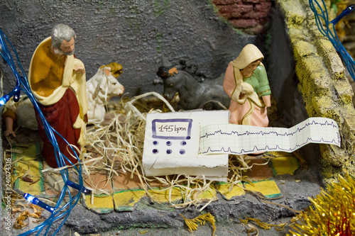 Obraz na płótnie Nativity scene during Advent with cardiotocograph/electronic fetal monitor (EFM) (a machine for recording the fetal heartbeat and the uterine contractions during pregnancy) instead of Baby Jesus