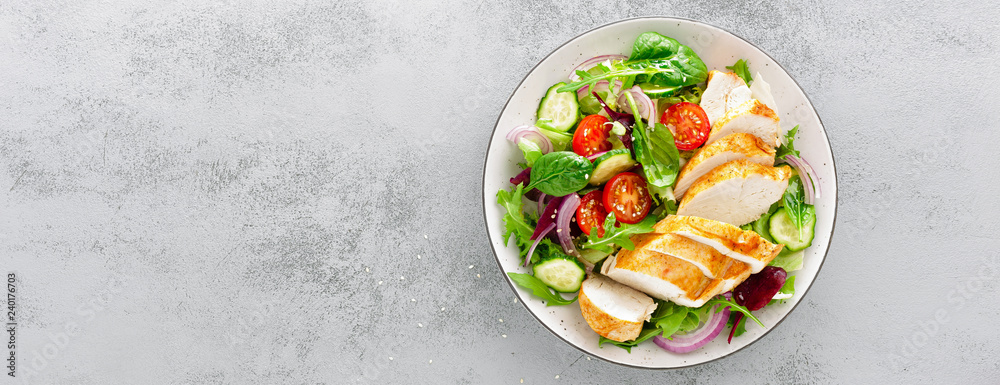 Fototapeta Grilled chicken breast, fillet and fresh vegetable salad of lettuce, arugula, spinach, cucumber and tomato. Healthy lunch menu. Diet food. Top view. Banner