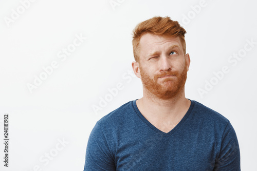 Redhead attractive male with bristle in casual blue t-shirt, pursing lips making hmm sound, closing one eye and looking up, thinking or making decision, trying calculate in mind or make up idea