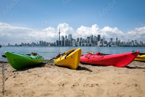 Tuinposter Toronto Colorful kayaks on a beach with Toronto skyline in background