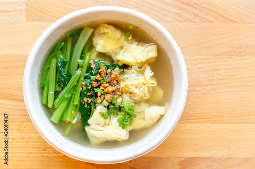 Wanton soup with morning glory and deep fried garlic in bio paper bowl on wooden background.