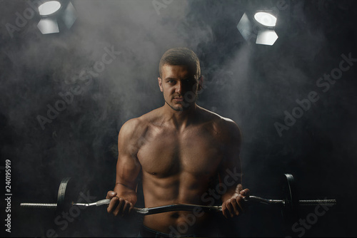 Fotografie, Obraz  young man with a barbell posing on a dark background