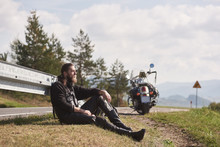 Tall Athletic Muscular Motorcyclist In Black Leather Clothing Sitting At Modern Powerful Cruiser Motorbike On Grassy Roadside On Blurred Background Of Sunny Distant Hills Under Bright Sky.