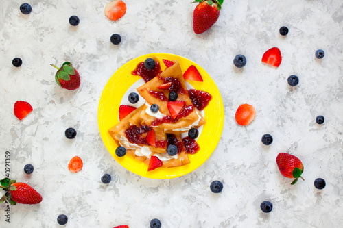 Fotografía  Two thin pancakes, folded in triangles, are poured with sour cream, jam and decorated with fresh berries surrounded by blueberries and strawberries