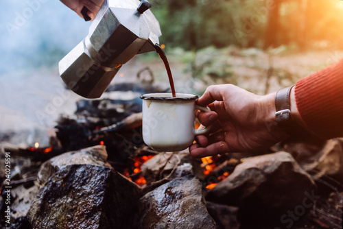 Fotografia, Obraz Tourists a sits near camp fire an in summer time and pours itself hot coffee during the sunset