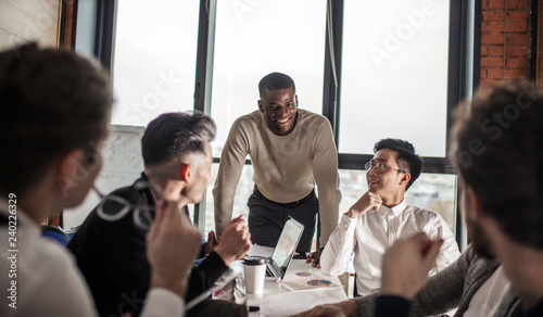 Fotografia, Obraz  African american business couch provides to a multiracial group of employees corporate training, Stress and work-life issues were integrated into the corporate learning plan