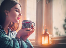 Beautiful Brunette Girl Drinking Coffee At Home, Looking Out The Window. Beauty Model Woman With The Cup Of Hot Tea