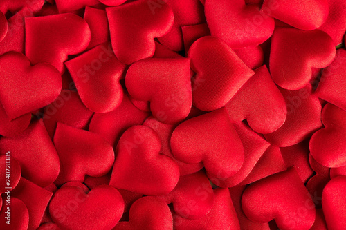 Valentine's Day. Red heart shape backdrop. Abstract holiday Valentine background with red satin hearts. Love concept