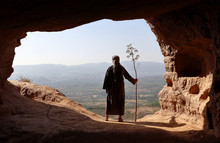 HERMIT  MAN LOOKING TO THE VALLEY FROM A HIGH CAVE WITH A BRANCH IN THE HAND IN SUMMER
