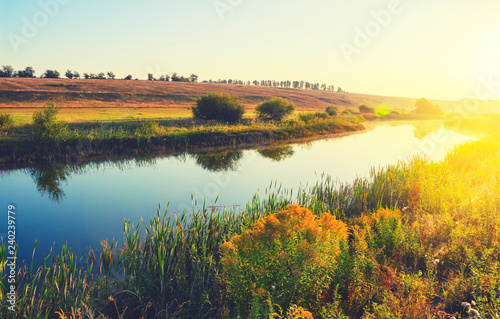 Fotografia  Sunny summer landscape with river flowing between the beautiful green hills,fields and meadows
