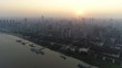 High angle drone shot of modern Wuhan (Hankou) skyline and Yangtze river at sunset, major city in China