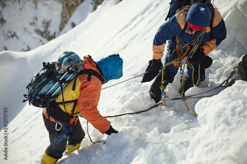 Spoed Fotobehang Alpinisme Two climbers on a snow-covered slope in the mountains closeup.