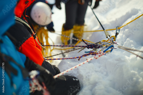 Fotoposter Alpinisme A group of climbers on a snow-covered mountain slope secured on a safety rope. Climbing station. Tilt-shift effect.