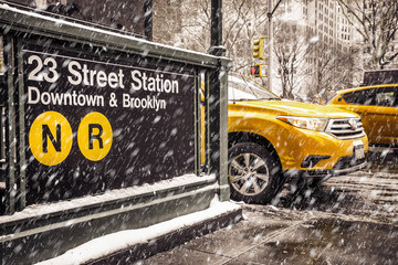 Midtown New York City Manhattan street scene at the 23rd subway street station with yellow taxi cab and snowflakes falling during winter snow storm