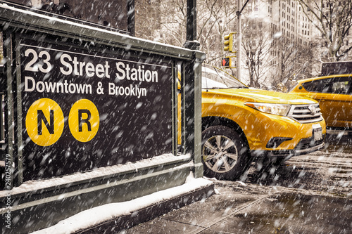 Staande foto New York TAXI Midtown New York City Manhattan street scene at the 23rd subway street station with yellow taxi cab and snowflakes falling during winter snow storm