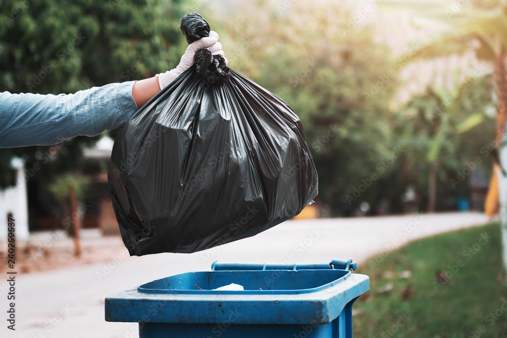 Fototapeta hand holding garbage black bag putting in to trash