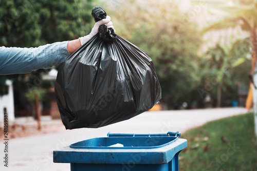 hand holding garbage black bag putting in to trash Wallpaper Mural