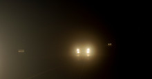 Bright Headlights Of A Car Driving On Foggy Road