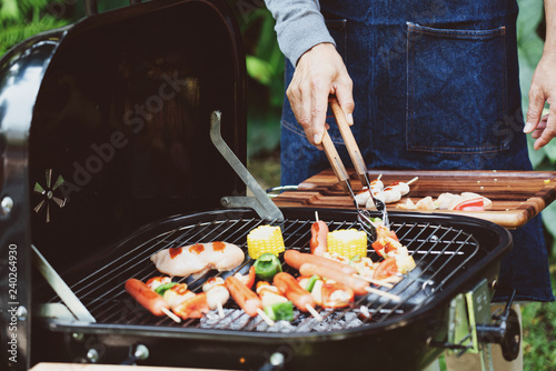 Photo Stands Grill / Barbecue Closeup at the hands of men Holding food tongs for making barbecue Which is a celebration during the weekend Within the family In important festivals such as birthdays, Christmas and Happy New Year