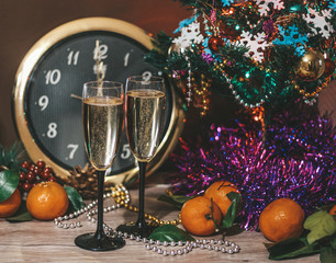 Christmas composition consisting of watches, glasses of champagne with bubbles, decorated Christmas tree, tangerines and other decorations
