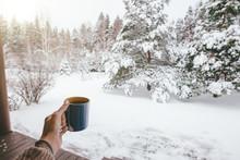 Holding Mug With Tea Over Snow...