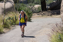 A Blonde Female Hiker Wearing A Backpack And Hiking Boots Walks Up An Old Fire Road On The Potato Chip Rock Trail Near Ramona, California In Southern California On A Hot Summer Day.