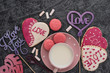 Romantic Valentine's Day breakfast. Heart-shaped cookies and a cup of milk on a gray table. Top view