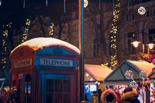 Winter Holidays Season Time At Night Urban Unfocused Background With Red Classic Phone Booth On Foreground