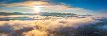 Aerial Panoramic View Of Golden Light On Morning Clouds In Blue Sky. Flight Through Moving Cloudscape With Beautiful Sun Rays. Use For Cinema Background.