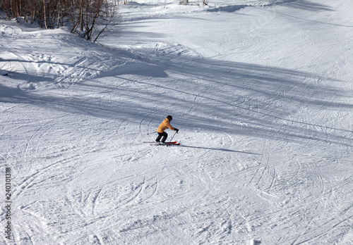 Skier descents on snowy ski slope at sun winter day