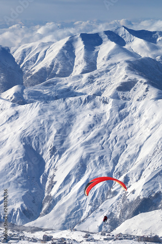 Speed flying at snowy mountains over ski resort at sunny winter day