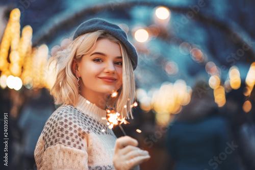 Fototapeta Happy smiling girl holding sparkler, posing at night Christmas fair
