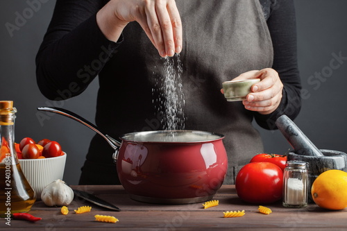 Fototapeta The chef preparations spaghetti and pasta, salt water, against a dark background, the concept of cooking. Woman salting water before cooking pasta fusilli obraz