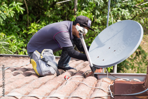 Photo Technician installing satellite dish and television antenna on roof top