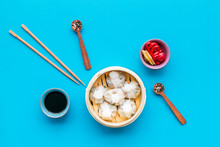 Dinner In Chinese Restaurant With Dim Sum, Sticks, Spices And Tea On Blue Background Top View