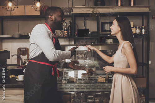 Fotografía  Male barista helps a girl to choose a dessert