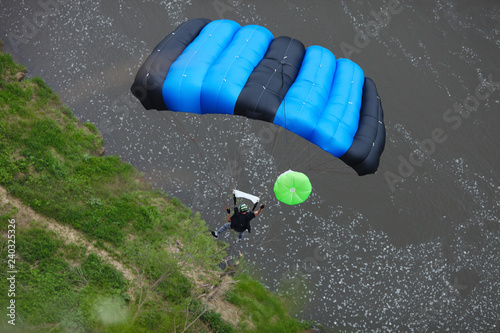 Base jumper under the canopy of a parachute lands on the banks of the river. View from above.