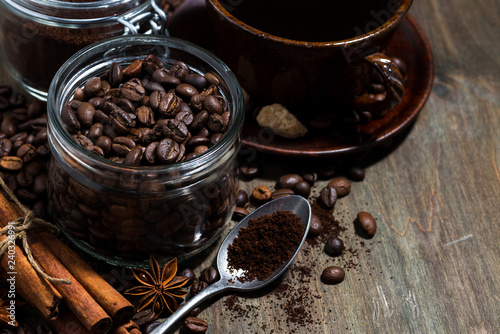 roasted coffee beans and spices on wooden background, concept photo, closeup