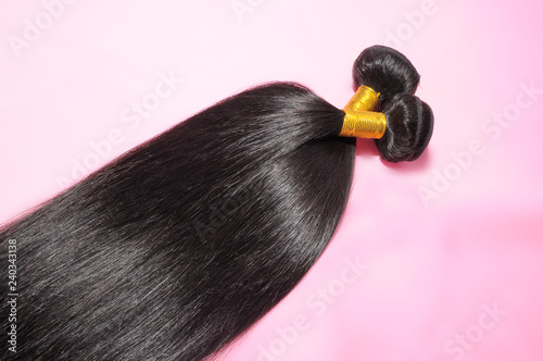 Photo straight black human hair weaves extensions bundle on pink background