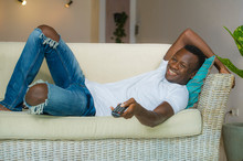 Young Attractive And Happy Black Afro American Man Holding TV Remote Controller Watching Television Movie Enjoying Relaxed Chilling At Living Room Lying At Home Couch
