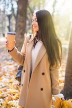 Attractive Woman Drinking Coffee To Go In Autumn Forest