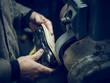 Crop shoemaker polishing sole of shoe