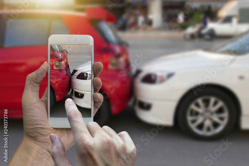 Close up hand holding smartphone and take photo at The scene of a car crash and Wallpaper Mural