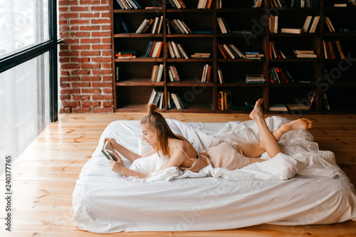 Fototapeta  Young girl in negligee reading book in bed